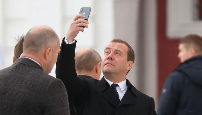 Премьер-министр России Дмитрий Медведев с смартфоном iPhone X во время посещения Воскресенского