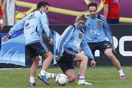 Хави (слева) пытается обыграть Фернандо Торреса (по центру)