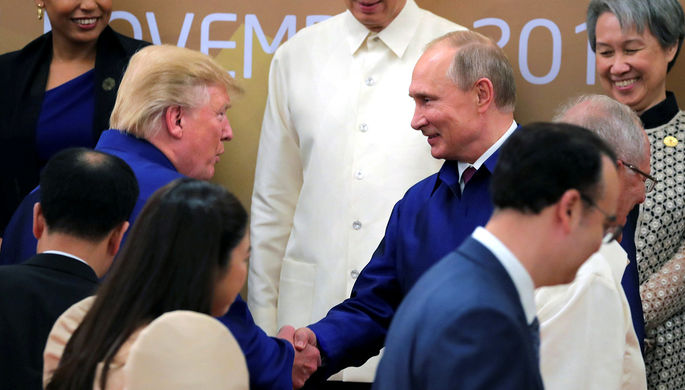 Президент США Дональд Трамп и президент России Владимир Путин пожимают руки во время встречи