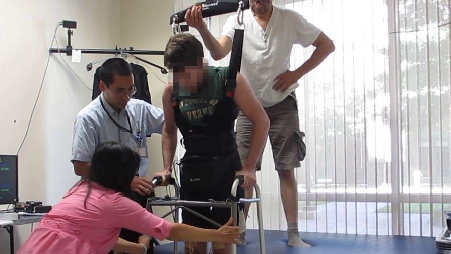 На пациента надевают систему, помогающую ему ходить