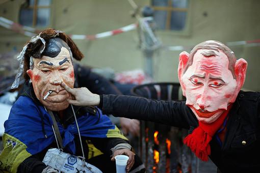 Люди на Майдане в масках Путина и Януковича