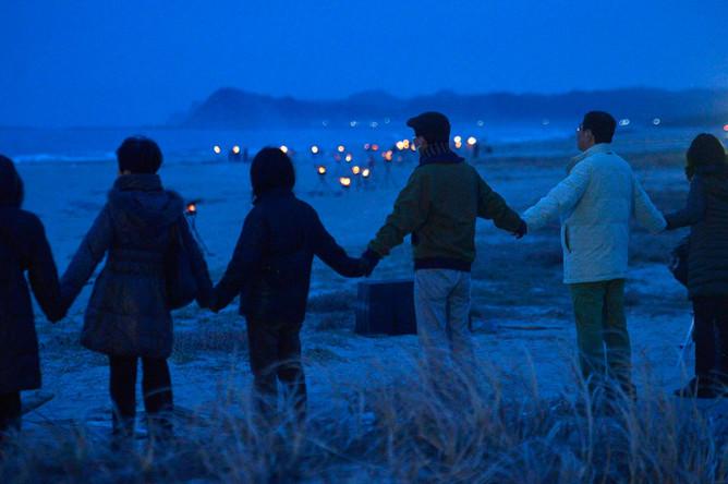 В Японии проходят траурные мероприятия. Еще накануне вечером люди вышли на берег Тихого океана, чтобы почтить память жертв – более 18 тысяч человек погибли и пропали без вести.