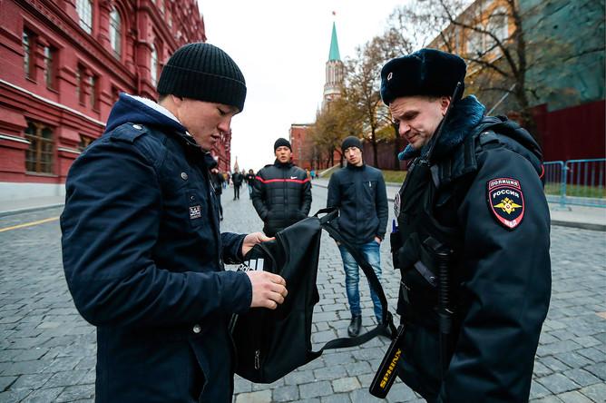 Сотрудник полиции проводит досмотр личных вещей прохожего у Государственного исторического музея