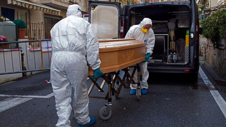 Медики во время транспортировки гроба с телом жертвы коронавируса COVID-19 в Лайгуэлье, 1 марта 2020 года