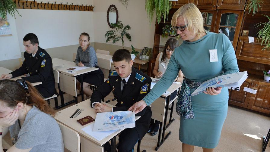 Преподаватель раздает конверты с контрольными измерительными материалами перед началом единого государственного экзамена по математике в средней образовательной школе №41 Челябинска
