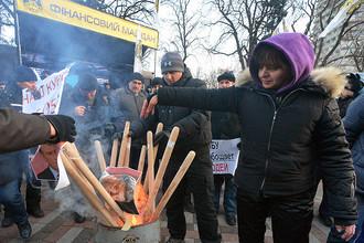 Участники акции протеста «Финансовый майдан» сжигают портрет президента Украины Петра Порошенко у здания Верховной рады Украины