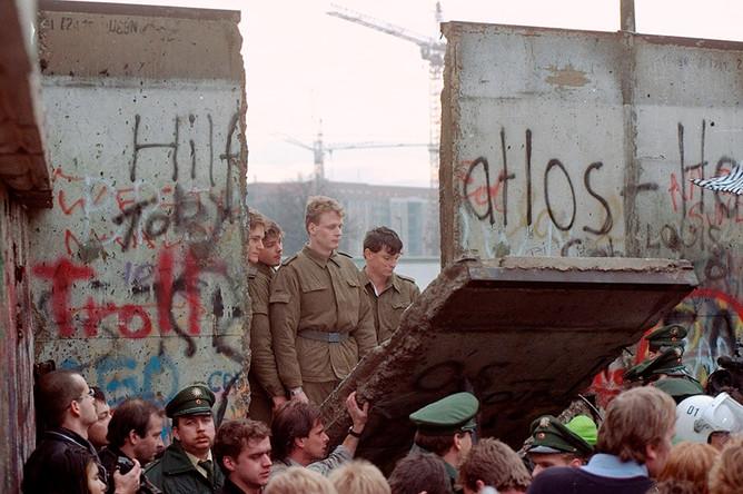 Восточногерманские пограничники стоят в проеме снесенной Берлинской стены возле Потсдамской площади, 11 ноября 1989 года