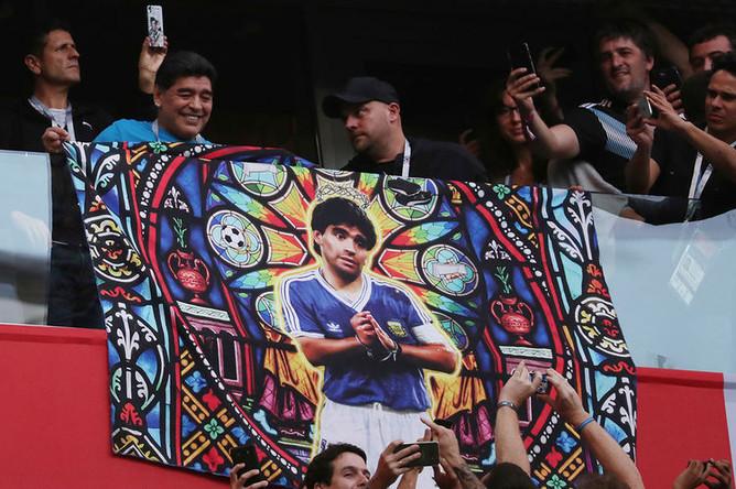 Диего Марадона с плакатом с собственным изображением перед матчем группового этапа чемпионата мира по футболу между сборными Нигерии и Аргентины в Санкт-Петербурге, 26 июня 2018 года