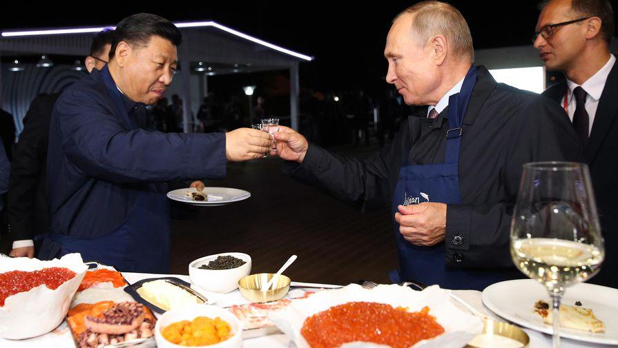 Председатель КНР Си Цзиньпин и президент РФ Владимир Путин (слева направо) во время посещения выставки «Улица Дальнего Востока» в рамках IV Восточного экономического форума на территории Дальневосточного федерального университета (ДВФУ) на острове Русский, 2018 год