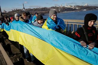Люди с национальными флагами в День соборности Украины в Киеве, январь 2017 года