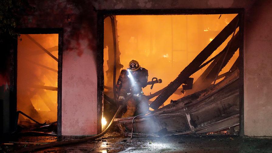 Пожарный борется с огнем в городе Санта-Кларита, Калифорния, 25 октября 2019 года