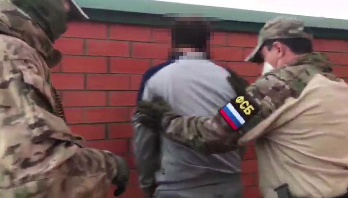 Сотрудник ФСБ РФ во время задержания гражданина, причастного к межрегиональному экстремистскому сообществу, запрещенному в России