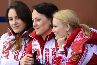 Слева направо: Анна Сидорова (Россия), Екатерина Галкина (Россия) и Александра Саитова (Россия) наблюдают за ходом матча кругового турнира между сборными командами России и Канады в соревнованиях по керлингу среди мужчин на XXII зимних Олимпийских играх в Сочи.