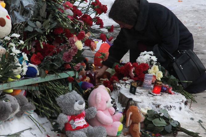 Женщина зажигает свечи неподалеку от места, где произошло обрушение одного из подъездов жилого дома в Магнитогорске, где произошел взрыв бытового газа, 2 января 2019 года