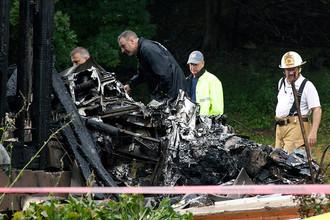 Пожарные и спасатели работают на месте крушения самолета упавшего на жилые дома в городе Ист-Хейвен