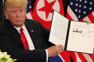 Президент США Дональд Трамп с подписанным документом после встречи с высшим руководителем КНДР Ким Чен Ыном в Сингапуре, 12 июня 2018 года
