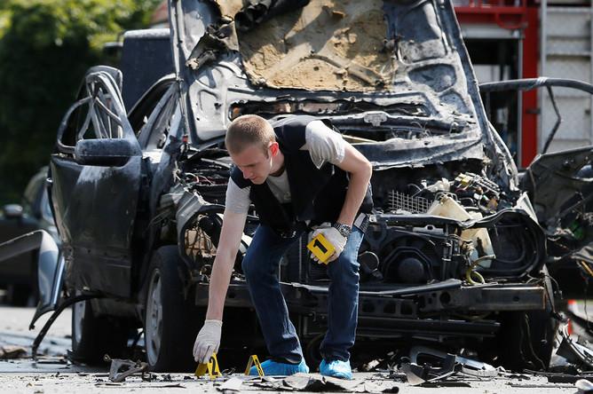 Следователи на месте взрыва машины в Киеве, 27 июня 2017 года