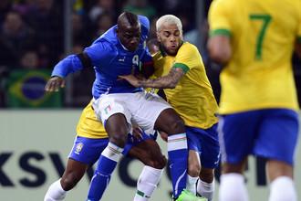 Итальянец Марио Балотелли ведет борьбу против бразильца Дани Алвеса