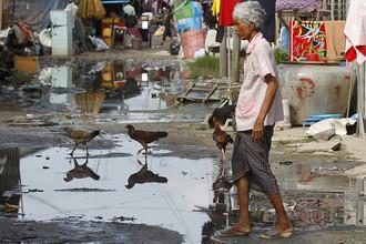 ВИЧ-инфицированная женщина рядом со своим домом на одной из улиц в столице Камбоджи