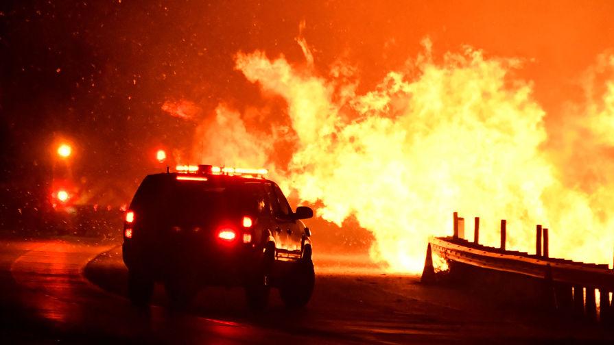 Пожарные борются с огнем в городе Санта-Кларита, который находится в 50 километрах от Лос-Анджелесе, 25 октября 2019 года
