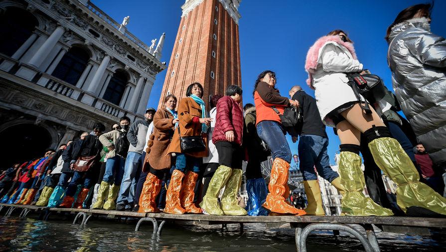 Туристы на затопленной площади Святого Марка в Венеции, 14 ноября 2019 года