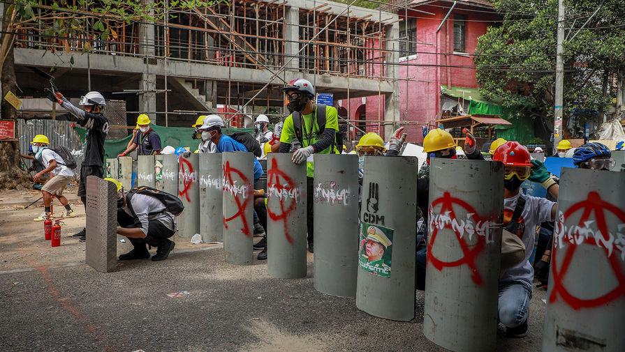 Протестующие с самодельными щитами во время столкновений с полицией в Янгоне, 3 марта 2021 года