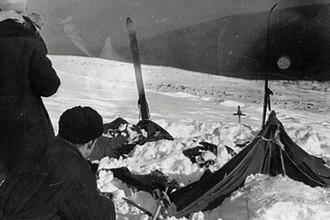 Палатка группы Дятлова, частично раскопанная от снега. Фото участника поисков А. С. Чеглакова (по другим сведениям, В. Д. Брусницына). Слева от палатки поисковики: Ю. Коптелов, за ним В. Карелин