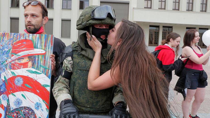 Сотрудник силовых структур Белоруссии и участница демонстрации около Дома правительства в Минске, 14 августа 2020 года