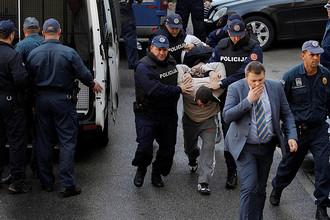 Сотрудники полиции Черногории ведут задержанного мужчину на судебное заседание в Подгорице, 16 октября 2016 года