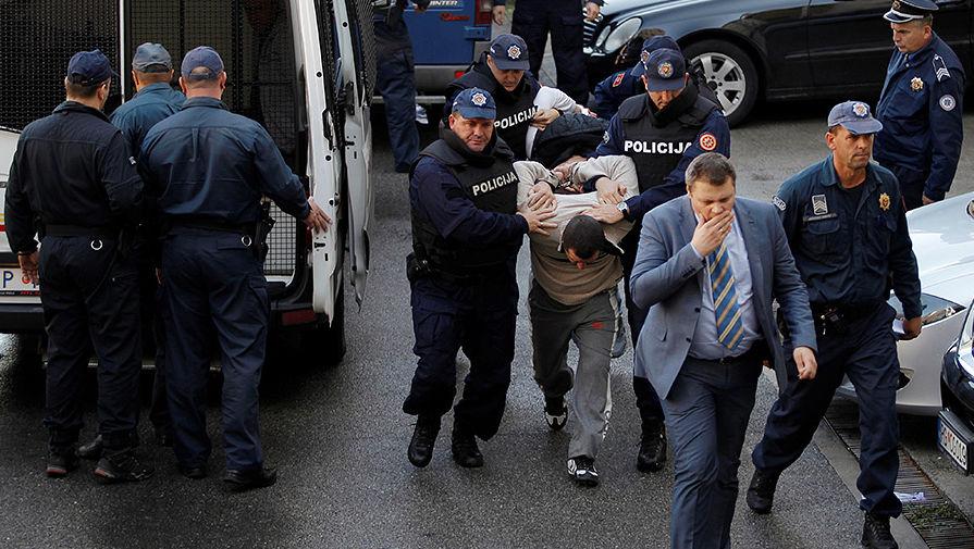 Сотрудники полиции Черногории ведут задержанного мужчину на судебное заседание в Подгорице, 16...