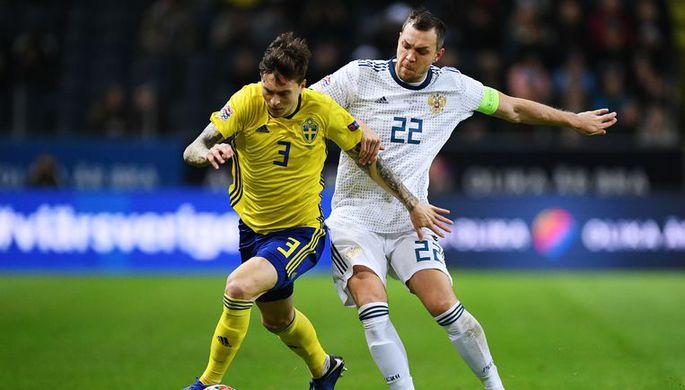 Защитний сборной Швеции Виктор Линделеф и капитан сборной России Артем Дзюба