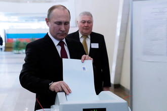 Действующий президент РФ, кандидат на пост президента РФ Владимир Путин во время голосования на выборах президента РФ на избирательном участке № 2151 18 марта 2018 года