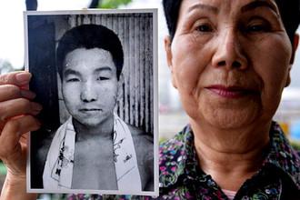 Сестра заключенного Хакамады держит фотографию брата