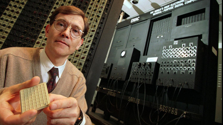 Профессор Ван дер Шпигель из Университета Пенсильвании демонстрирует микропроцессор (черная точка на панели в его руке) на фоне примерно одной десятой части первого в мире электронного компьютера (ENIAC), 1996 год