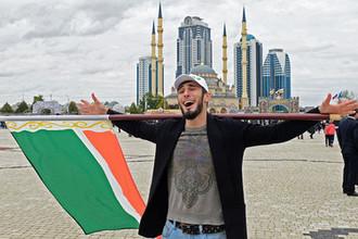 Мужчина с флагом Чеченской Республики на площади имени Ахмата Кадырова