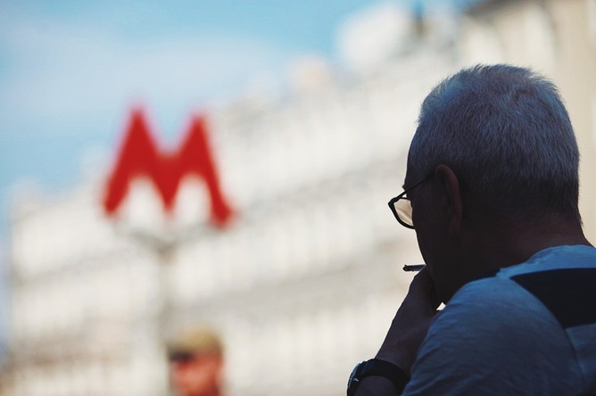Мужчина курит у входа на станцию метро «Чеховская»