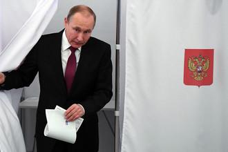 Действующий президент РФ, кандидат на пост президента РФ Владимир Путин во время голосования на выборах президента РФ на избирательном участке № 2151, 18 марта 2018 года