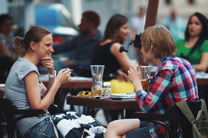 Посетители курят на летней веранде кафе в Камергерском переулке