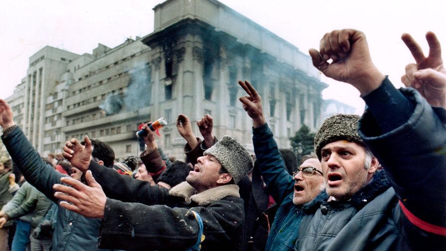 Протестующие против режима перед горящим зданием на площади Республики, 24 декабря 1989 года