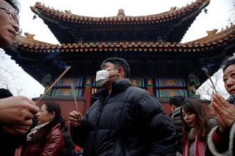 Люди зажигают ароматические палочки и молятся за удачу в храме Юнхэгун Лама в первый день лунного нового года Петуха в Пекине, Китай