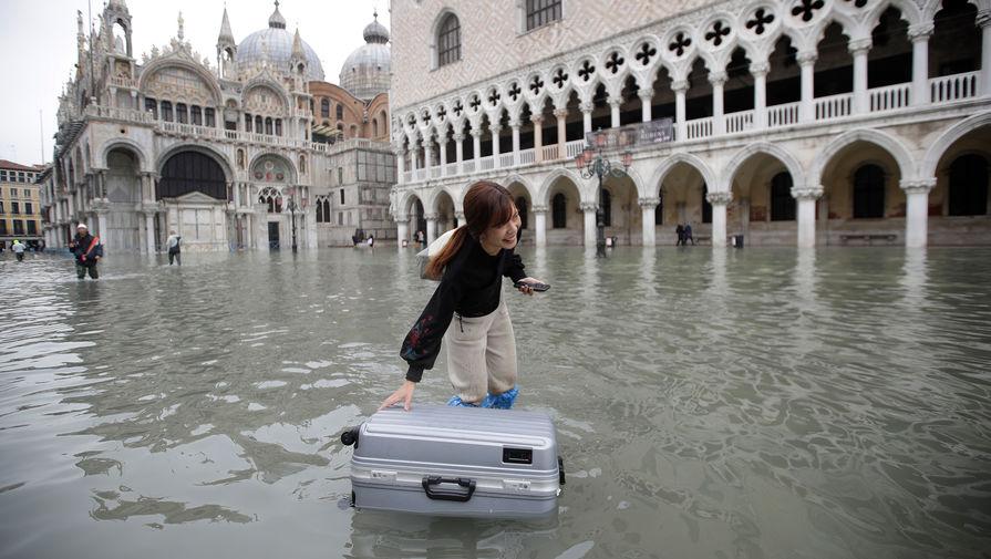 Туристка со своим чемоданом на затопленной площади Святого Марка в Венеции, 13 ноября 2019 года