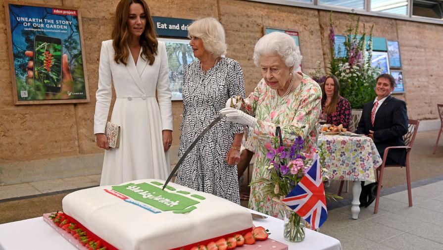 Королева Великобритании Елизавета II разрезает торт церемониальной саблей в ботаническом саду «Эден» в графстве Корнуолл. Рядом — герцогиня Кембриджская Кэтрин и герцогиня Корнуолльская Камилла