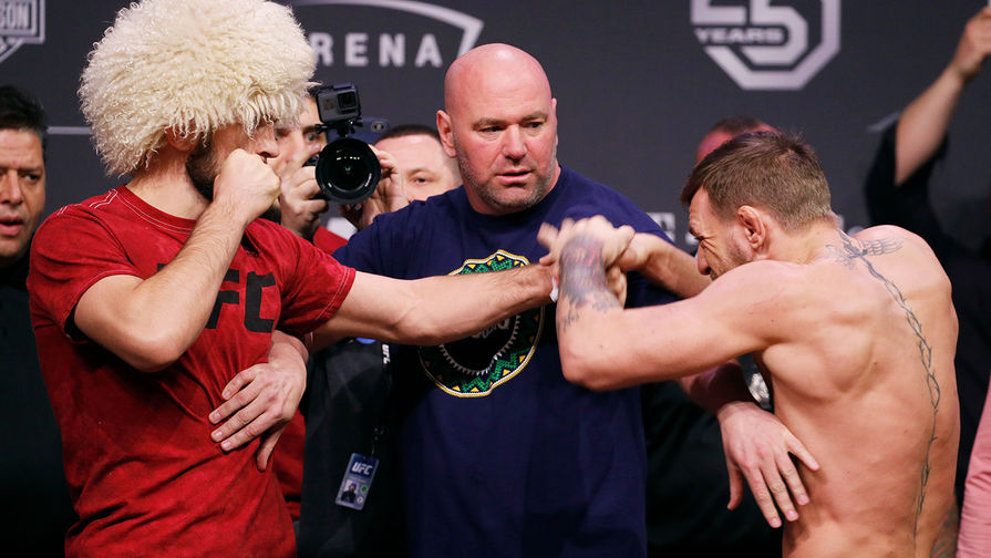 Conor McGregor, right, knocks away Khabib Nurmagomedov's hand during a... 2