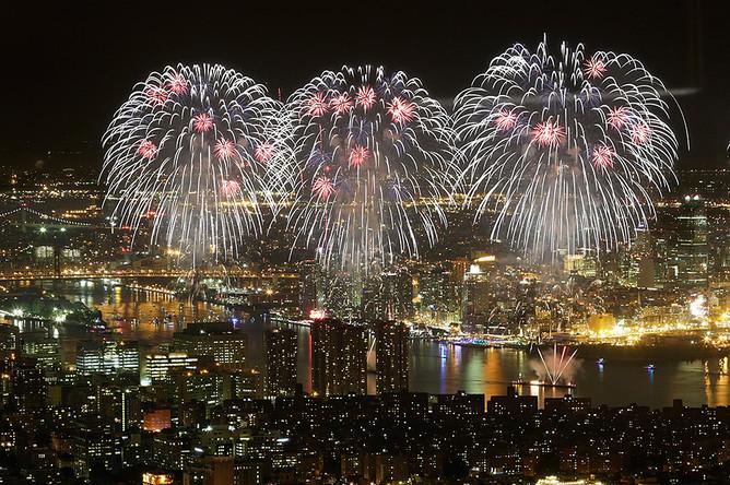Праздничный фейерверк освещает небо над Ист-Ривер в Нью-Йорке