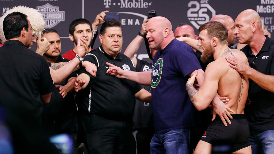 People pull apart Khabib Nurmagomedov, left, and Conor McGregor,... 3