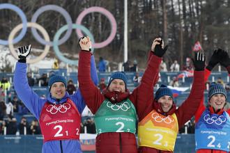 Российские лыжники Андрей Ларьков, Денис Спицов, Александр Большунов и Алексей Червоткин празднуют серебро в эстафете на Олимпиаде-2018