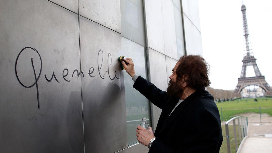 Известный французский писатель Марек Хальтер стирает с Парижской Стены Мира слово...