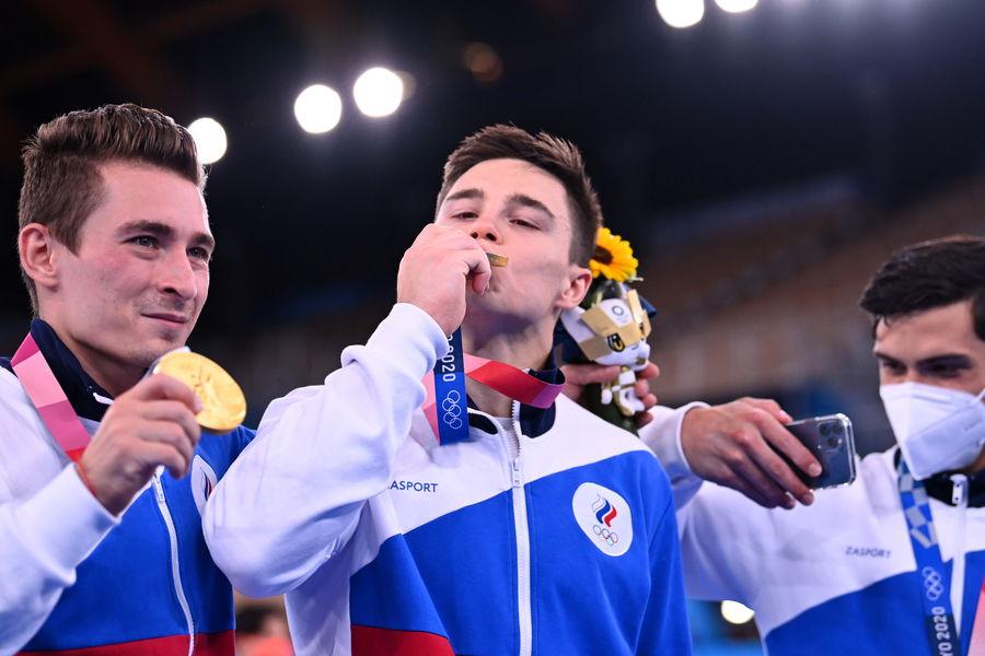 Российские спортивные гимнасты Никита Нагорный, Давид Белявский и Артур Далалоян нацеремонии награждения после победы вкомандном многоборье наОлимпийских играх вТокио