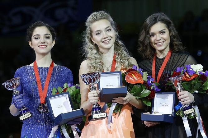 Российские фигуристки Евгения Медведева, Елена Радионова и Аделина Сотникова (слева направо) во время церемонии награждения на 5-м этапе серии Гран-при по фигурному катанию в спорткомплексе «Лужники»
