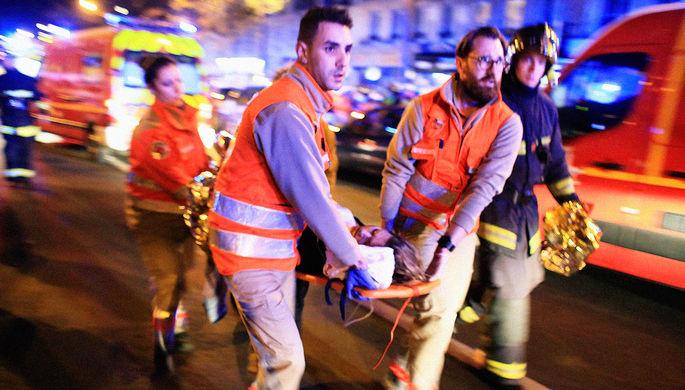 Пострадавшая женщина и медики около театра «Батаклан» после теракта в Париже, 13 ноября 2015 года